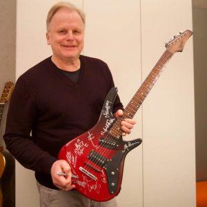 Herbert Grönemeyer hält die Gitarre mit seiner Unterschrift hoch.